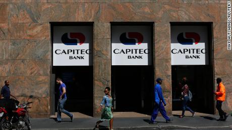 Pedestrians walk past a branch of Capitec Bank in Cape Town.
