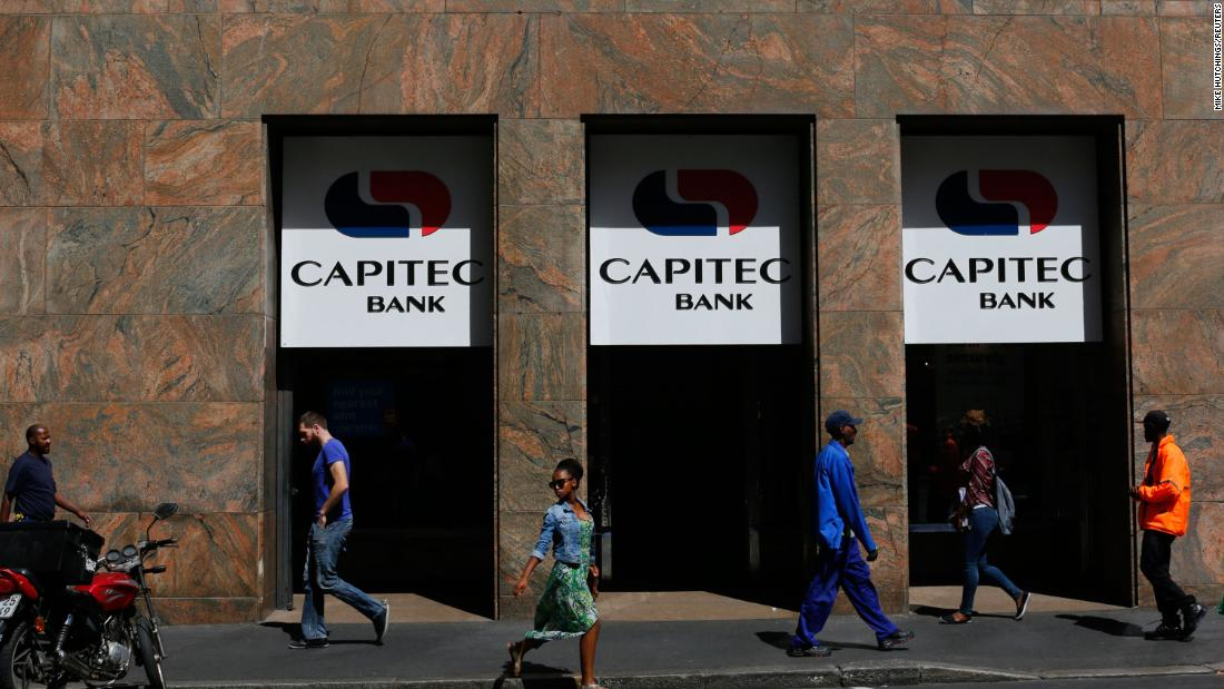 Pedestrians walk past a branch of Capitec Bank in Cape Town.