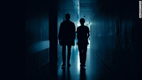 Medical Staff Silhouettes Walk in Dark Part of the Hospital Corridor.; Shutterstock ID 1189798162; Job: CNN Photos