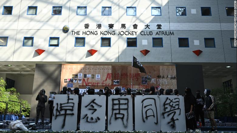 Students of Hong Kong University of Science and Technology (HKUST) hold signs mourning Chow Tsz-lok in Hong Kong on November 8, 2019.