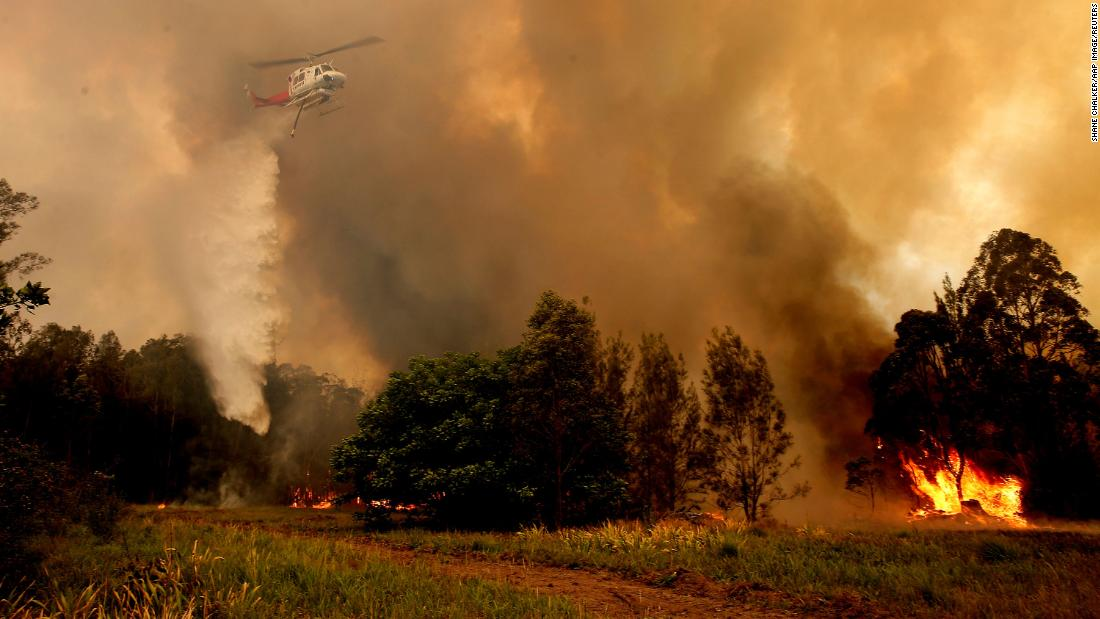 A helicopter drops water on a bushfire in Old Bar, New South Wales, Australia, on Saturday, November 9.