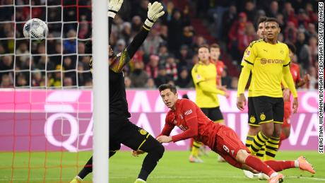 Robert Lewandowski heads Bayern Munich ahead against Borussia Dortmund as he maintained his record of scoring in every Bundesliga match since the start of the season.