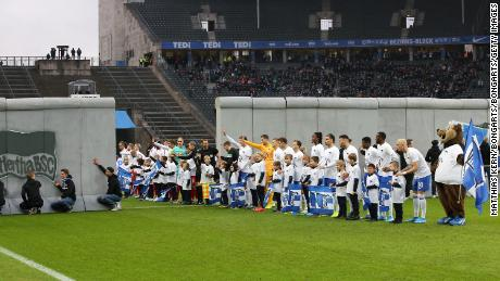 Players from Hertha Berlin and RB Leipzig line up on either side of a replica of the Berlin Wall before a Bundesliga match at the Olympic Stadium held on the 30th anniversary of the fall of the original wall.