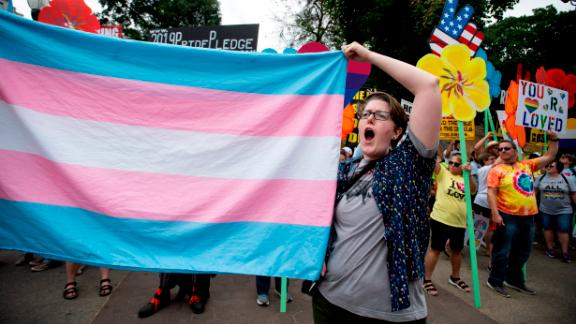 A supporter for the transgender community holds a trans flag in front of counter-protesters to protect attendees from their insults and obscenities at Atlanta's Gay Pride Festival on Saturday, October 12, 2019.
