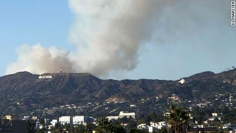 The Barham Fire sends smoke aloft from just behind the Hollywood sign in Los Angeles, California.