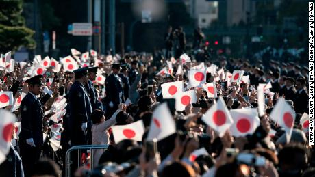 Spectators calm down Japanese flags as the motorcade passes.