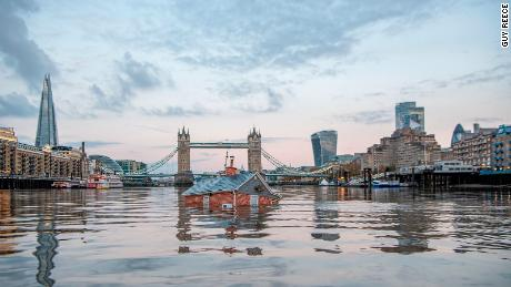 Extinction Rebellion activists floated a submerged replica of a suburban house down the River Thames in protest over rising sea levels.