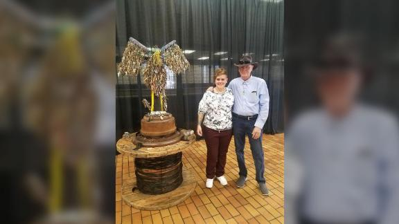 Jessie Mercer and her father, Tommie Mercer, pose next to Jessie's phoenix sculpture after the unveiling ceremony on Friday.