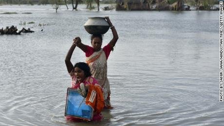 Women carry their belongings from a house submerged in water in the aftermath of Cyclone Bulbul, at Amarabati village in Bakkhali, South 24 Parganas district of India's West Bengal state on November 10, 2019.