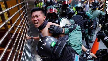 A protester is detained in Central district of Hong Kong on Monday, Nov. 11, 2019. A Hong Kong protester was shot by police Monday in a dramatic scene caught on video as demonstrators blocked train lines and roads during the morning commute.