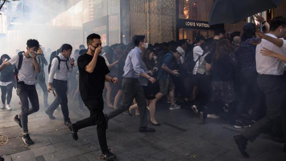 People run into a mall after police fired tear gas in the Central district of Hong Kong on November 11.