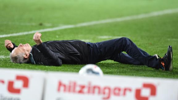 Freiburg manager Christian Streich is knocked to the ground by David Abraham.