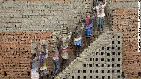 Indian labourers carry clay bricks to a brick kiln in Farakka, in the Indian state of West Bengal,  2019.