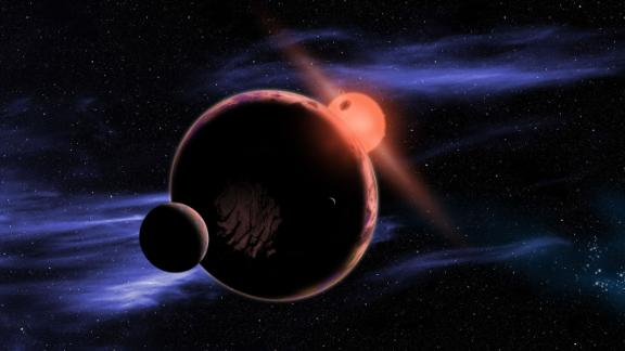This artist's concept illustration shows an exoplanet with two moons orbiting within the habitable zone of a red dwarf star.