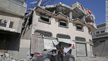 A Palestinian militant stands guard outside the house where Islamic Jihad leader Baha Abu Al-Ata was killed in a strike in Gaza.