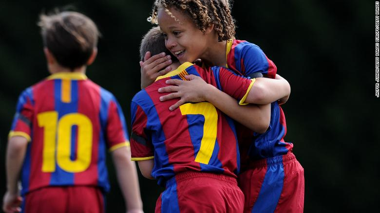 An eight-year-old Xavi Simons (right) celebrates a goal with a teammate during a 2011 match for FC Barcelona's youth team.