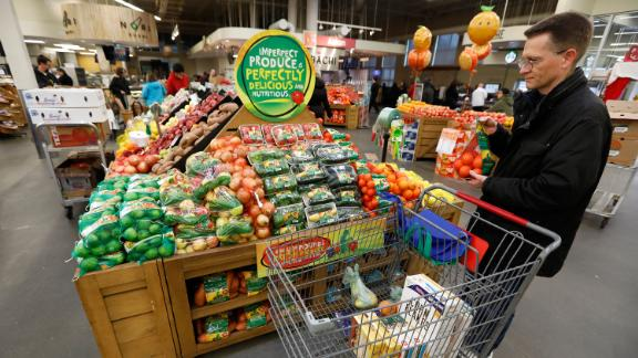 """In this Friday, Jan. 18, 2019, photo, Brian Tice, of Urbandale, Iowa, looks at the imperfect produce display at the Hy-Vee grocery store in Urbandale, Iowa. """"I like the cost savings and it is good to help and not throw so much away,"""" said Tice, who bought a pack of small oranges. (AP Photo/Charlie Neibergall)"""