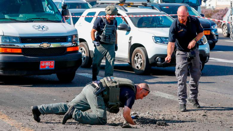 Israeli police inspect a hole in the highway in Ashdod on November 12.