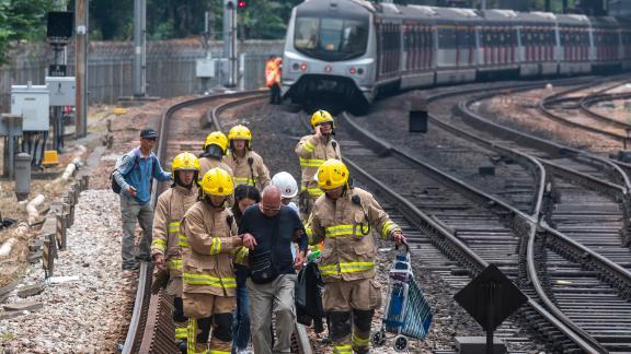 A man is escorted by firemen along train tracks near Sha Tin MTR station on November 12, 2019.