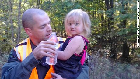 Michigan conservation officer Jeff Ginn holds Amber Smith, just after he located her in October 2013. Amber disappeared from her Barton Township home and Michigan Department of Natural Resources conservation officers were called in to assist with the search.