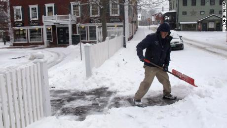 Bill Langley is trying to clear a snow blanket from the Green Mountain Inn in Stowe, Vermont.