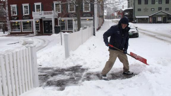 Bill Langley, of the Green Mountain Inn, in Stowe, Vermont, shovels snow from a sidewalk on Tuesday.