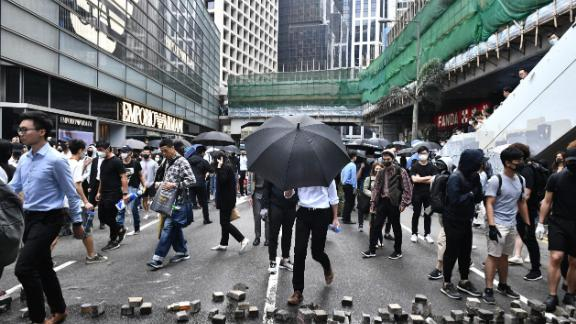 Office workers and pro-democracy protesters walk around bricks lying on a street during a demonstration in Central in Hong Kong on November 12, 2019.