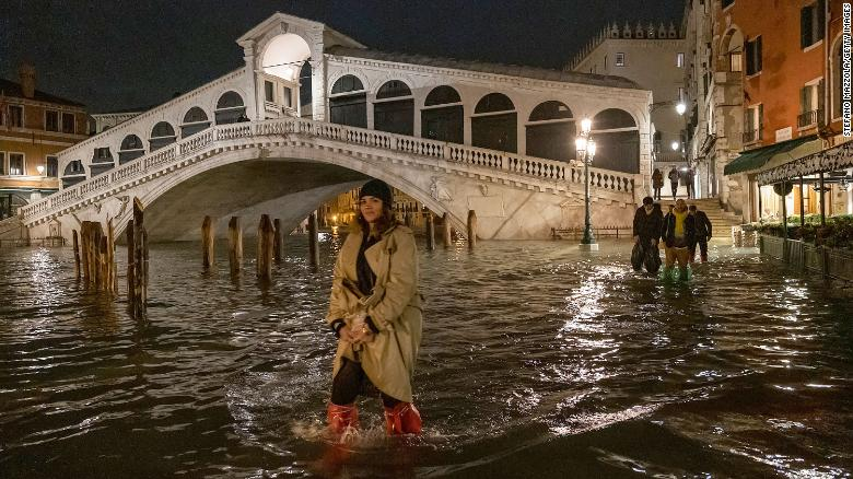 A tourist walks near the Rialto bridge after the passage of the exceptional high tide that reached 187 cm on November 12, 2019 in Venice, Italy.