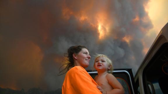 Residents look on as thick smoke rises from bushfires near Nana Glen on November 12.