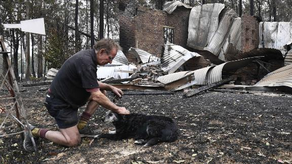 Warren Smith pats his dog after returning to find his house destroyed near Nana Glen on November 13.