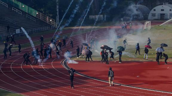 Students attempt to clear tear gas canisters fired by riot police onto a sports track during a confrontation at the Chinese University in Hong Kong on Tuesday, November 12.