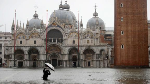 A photographer takes pictures in a flooded St. Mark's Square, in Venice, Italy, Tuesday, Nov. 12, 2019. The high tide reached a peak of 127cm (4.1ft) at 10:35am while an even higher level of 140cm(4.6ft) was predicted for later Tuesday evening. (AP Photo/Luca Bruno)