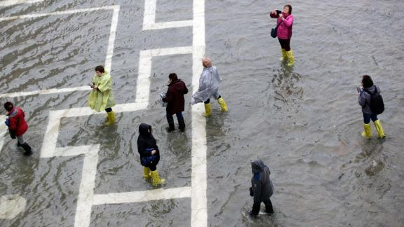 People walk through flood waters in St. Mark's Square on Tuesday.