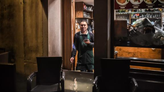 A man stands inside a restaurant barricaded from the flooding on November 12.
