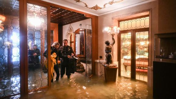An employee of the Gritti Palace helps a customer navigate a flooded entrance on November 12.