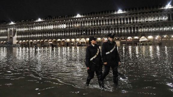 Police officers patrol a flooded St. Mark's Square during the high tide on November 12.