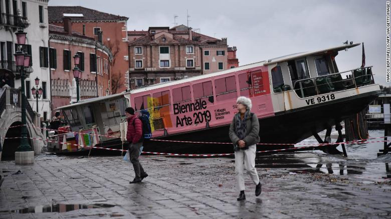 People walk past a stranded taxi boat on Riva degli Schiavoni, after it was washed away during an exceptional overnight high tides, early on Wednesday, November 13.