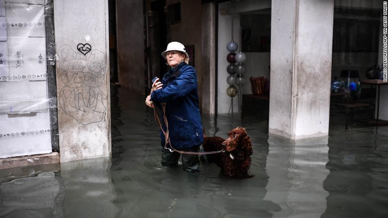 A woman walks her dog through a flooded street on November 13.