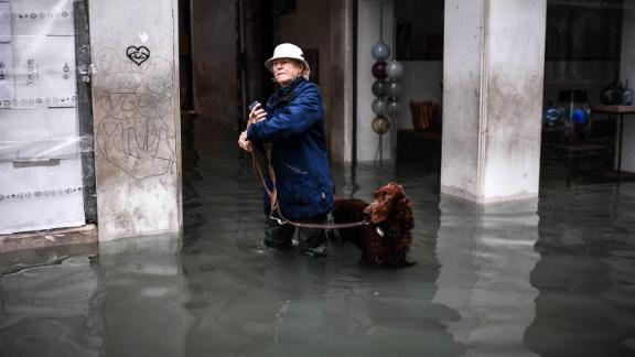 A woman walks her dog through a flooded street on November 13.