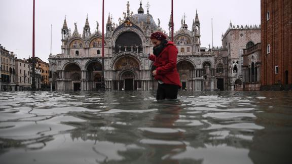 A woman crosses a flooded St. Mark's Square on November 13, after an exceptionally high tide inundated the area overnight.