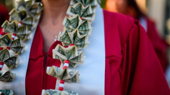 "A graduating student wears a money lei, a necklace made of US dollar bills, at the Pasadena City College graduation ceremony, June 14, 2019, in Pasadena, California. - With 45 million borrowers owing $1.5 trillion, the student debt crisis in the United States has exploded in recent years and has become a key electoral issue in the run-up to the 2020 presidential elections. ""Somebody who graduates from a public university this year is expected to have over $35,000 in student loan debt on average,"" said Cody Hounanian, program director of Student Debt Crisis, a California NGO that assists students and is fighting for reforms.  (Photo credit should read ROBYN BECK/AFP/Getty Images)"
