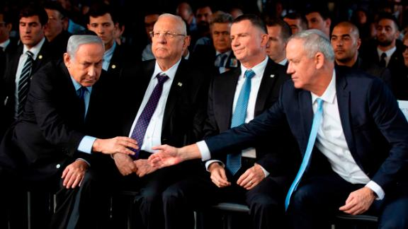 Netanyahu and Israeli Blue and White party chief Benny Gantz reach to shake hands during a state memorial ceremony for former Israeli Prime Minister Yitzhak Rabin and his wife Leah in Jerusalem on November 10. Exit polls for a repeat general election in September failed to give either of the political rivals a majority in the new parliament.