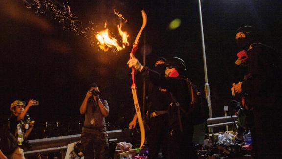 A protester releases a flaming arrow to light a barricade at The Chinese University of Hong Kong (CUHK), Wednesday, November 13.