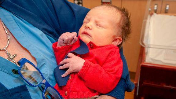 A baby at the West Penn Hospital is dressed up in a red cardigan and tie to celebrate World Kindness Day and Cardigan Day in honor of Mister Rogers.