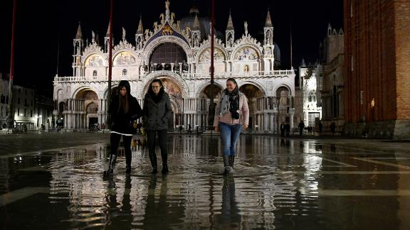 People walk across the partially flooded St. Mark