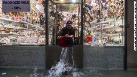 A shopkeeper throws out water from his shop during an exceptional high tide on November 13 in Venice.