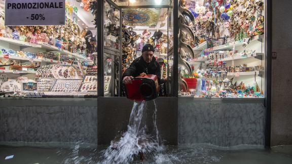 A shopkeeper throws out water from his flooded store on Wednesday, November 13.