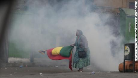 13 November 2019, Bolivia, La Paz: An indigenous woman, demanding the resignation of the current interim president Añiez, is standing with a flag in tear gas smoke. In the face of mass demonstrations and violent clashes, the new interim president of Bolivia, Anez, has called on her compatriots to unite. Photo: Gaston Brito/ (Photo by Gaston Brito/picture alliance via Getty Images)