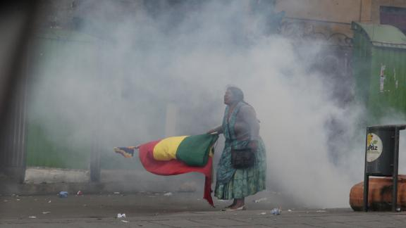 An indigenous protester is standing with a flag in tear gas smoke during Wednesday's unrest in La Paz.