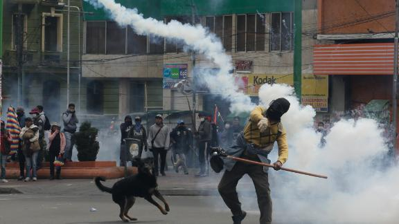 A demonstrator throws a smoking container during clashes with police in La Paz Wednesday.
